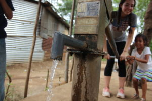 This is one of the local water pumps, where Jamie is helping pump water.