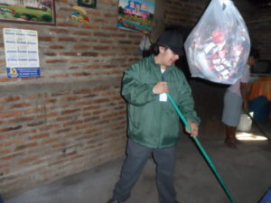 Carlos sweeping loose dirt to pack into worn down areas of the floor