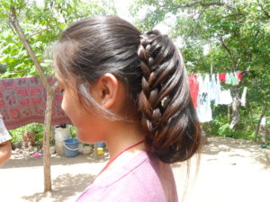 Stylishly braided hair by Aldina Aguilar, a woman from the community