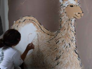 Nickole painting an alpaca